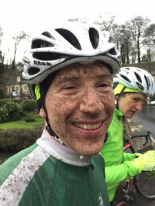 The face of a tired and muddy but happy cyclist